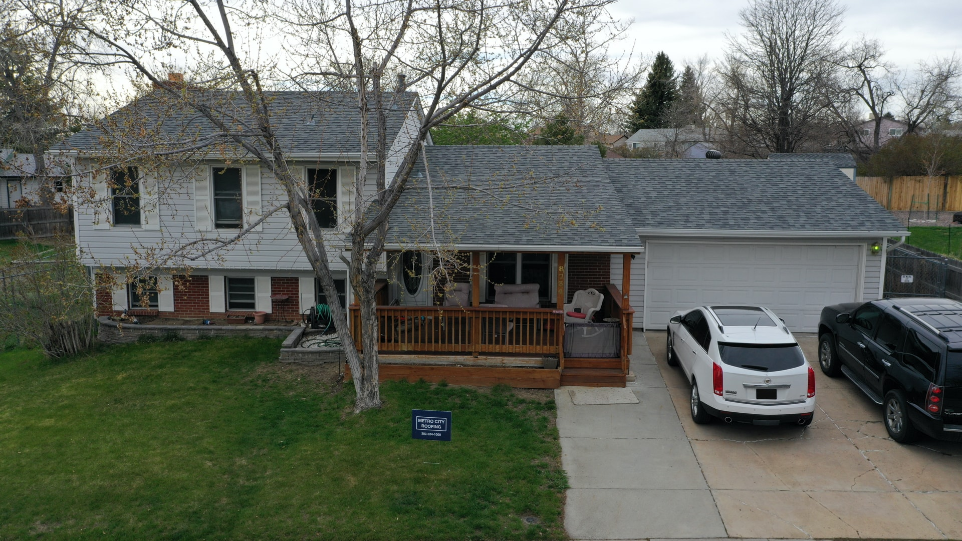 Gray, ranch style home with brown wood front porch in Westminster, Colorado with blue Metro City Roofing sign in the foreground