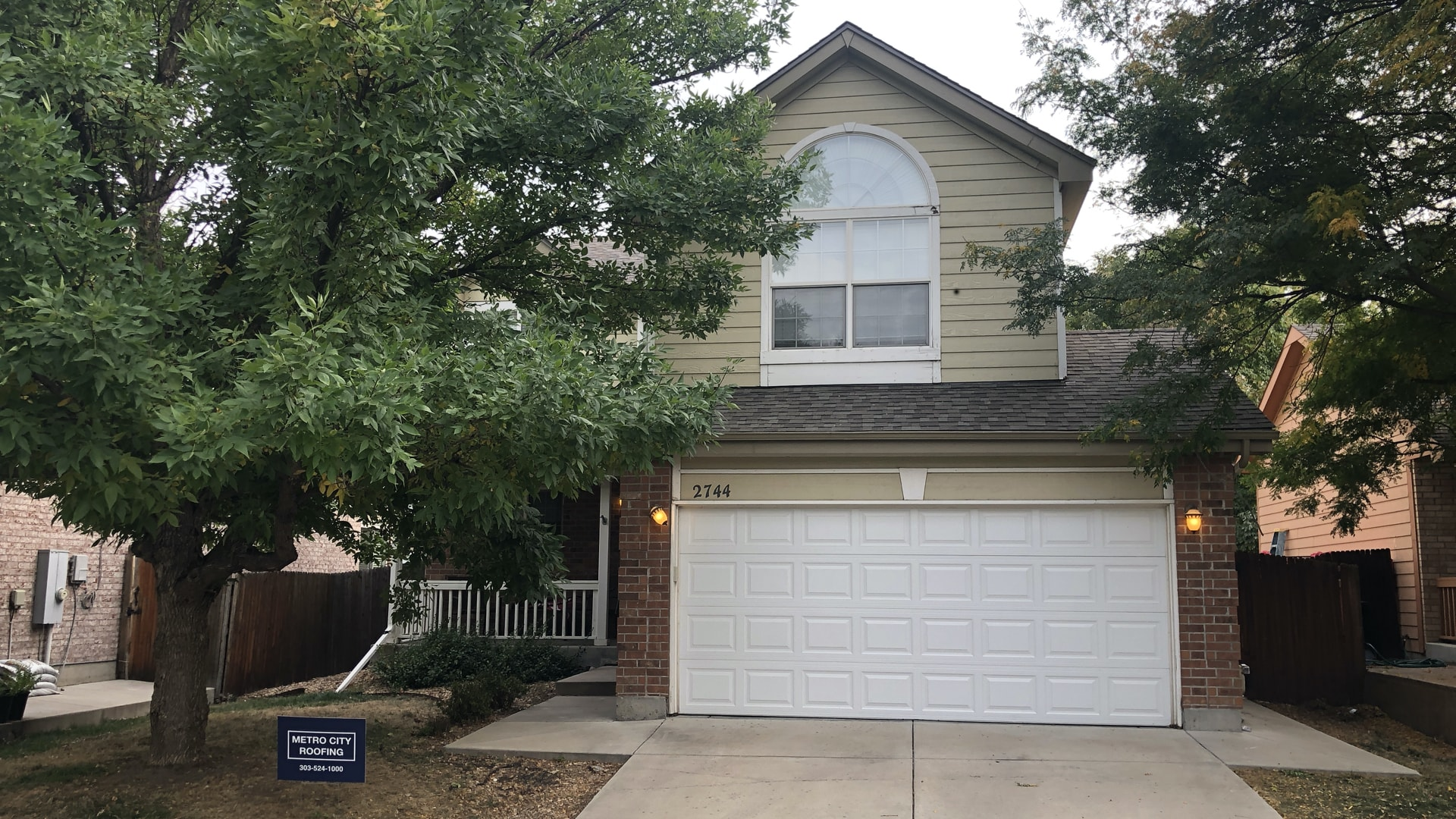 2-story home with beige siding and white garage with large tree and blue Metro City Roofing sign in the front yard