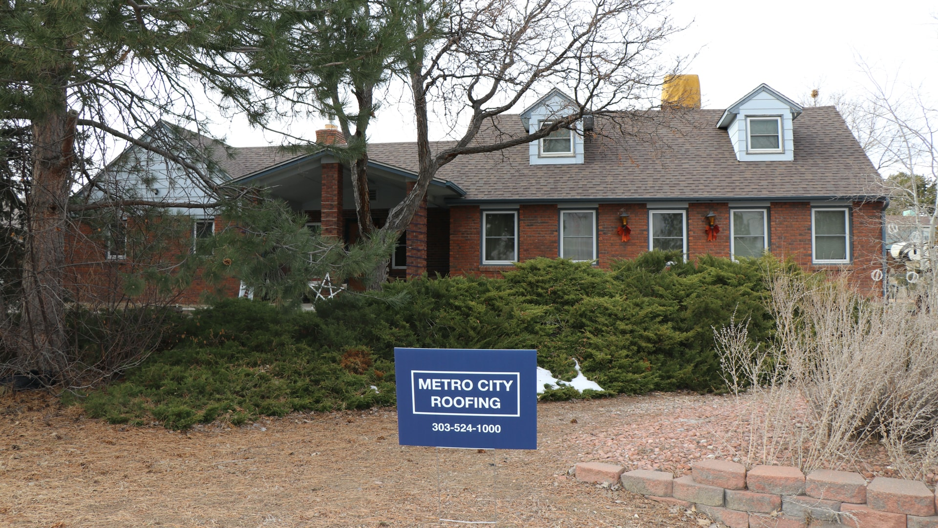 Red brick, ranch style home in Westminster, Colorado and blue Metro City Roofing sign in the foreground