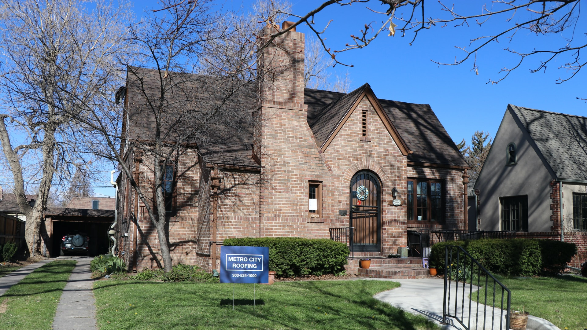 Brown brick, Tudor-style home with steep pitch and brown asphalt shingle roof in Denver, Colorado with blue Metro City Roofing sign in the foreground