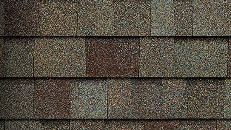 Multi-colored asphalt shingle with tan, brown, and light green flecks