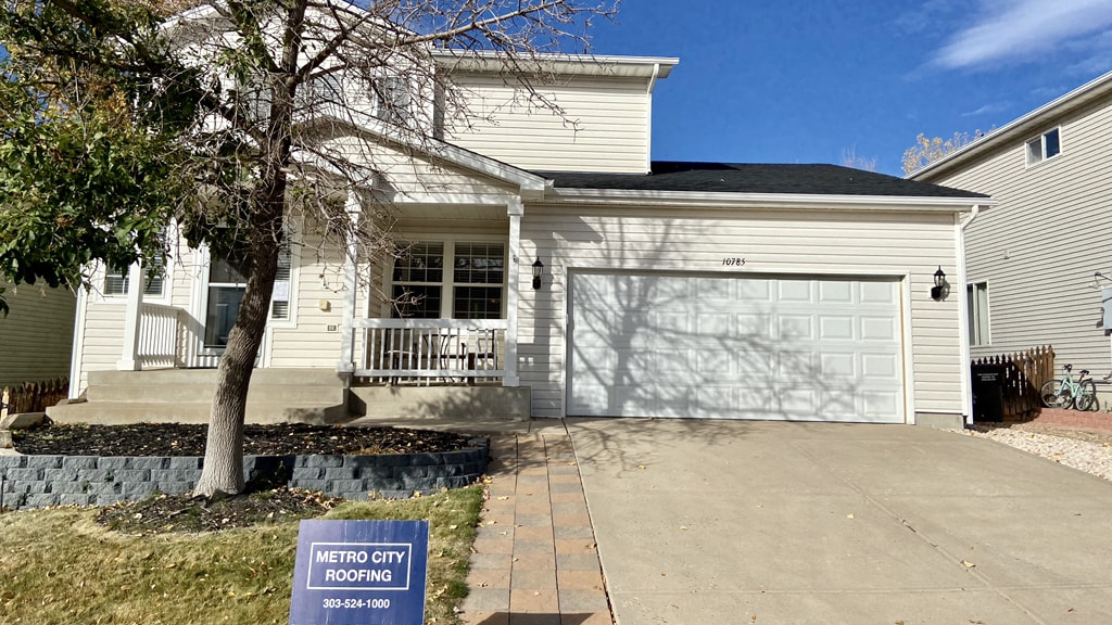 2-story home with cream colored siding and black shingle roof in Parker, Colorado with blue Metro City Roofing sign in the foreground