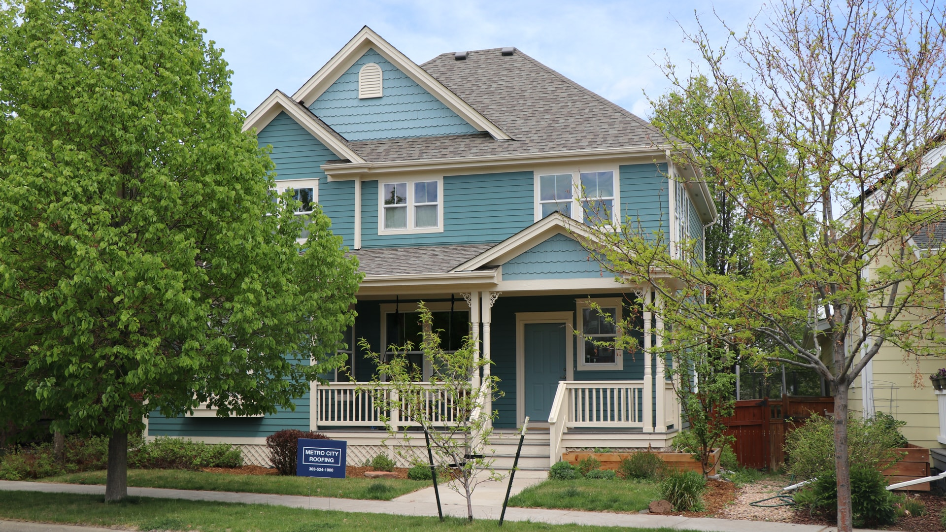 Green, Victorian style home in the Central Park neighborhood of Denver, Colorado with blue Metro City Roofing sign in the foreground