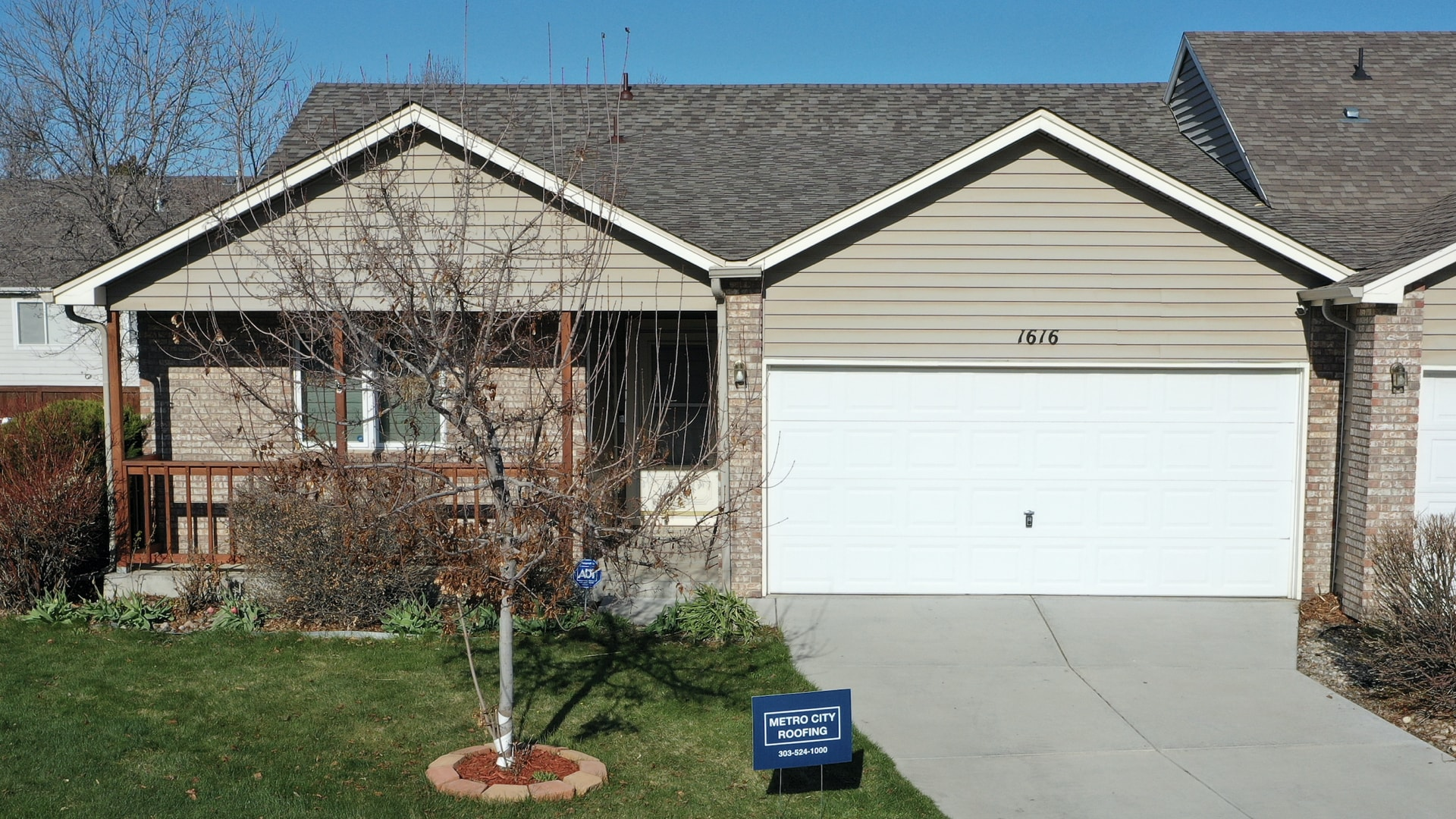 Beige, ranch style duplex in Loveland, Colorado with blue Metro City Roofing sign in the foreground