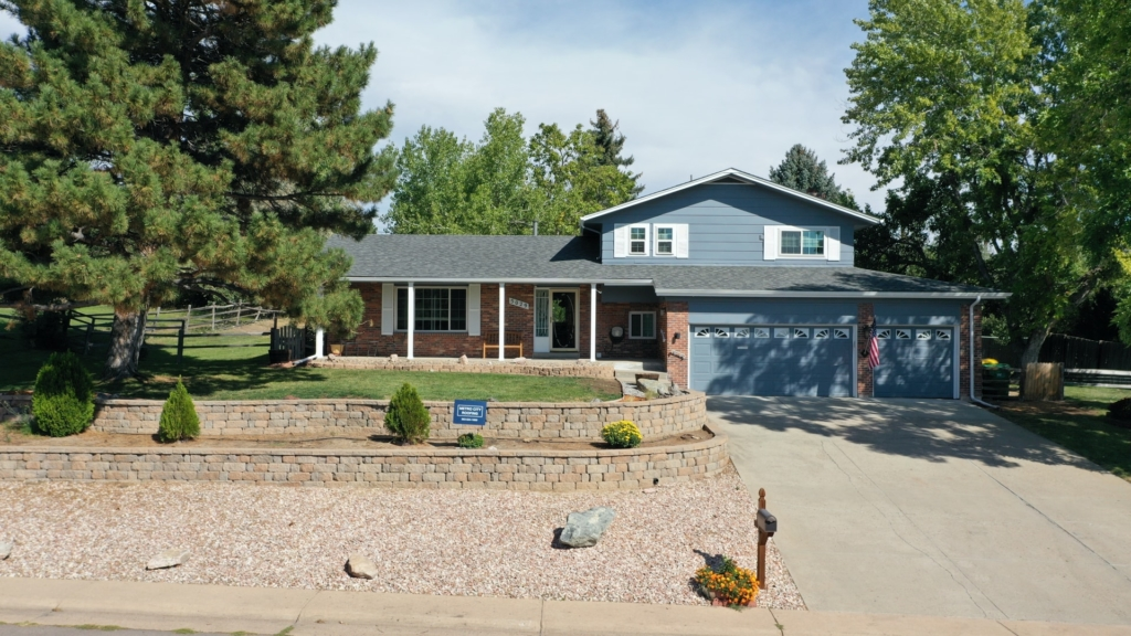 Gray, split-level home in Littleton, Colorado with blue Metro City Roofing sign in the foreground