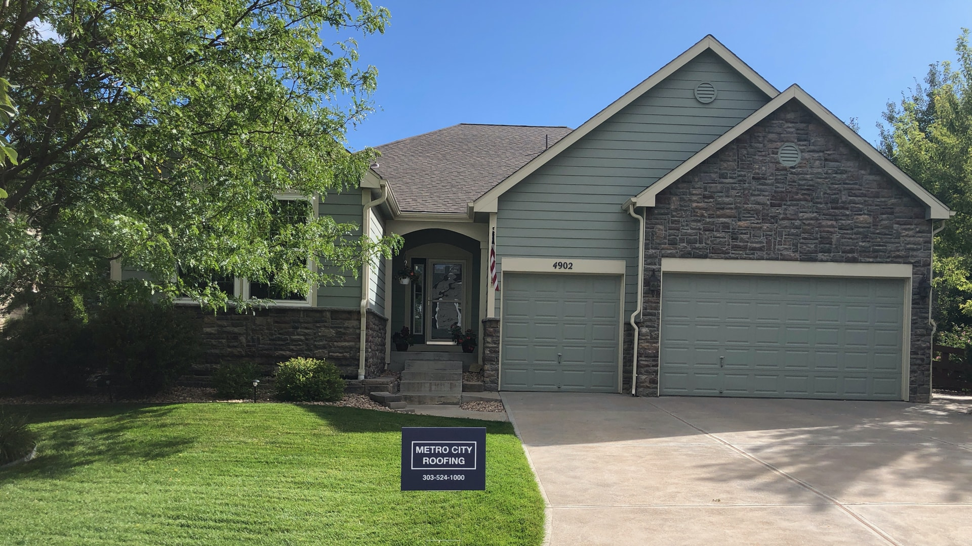 Green, ranch style home with stone accents in Broomfield, Colorado with blue Metro City Roofing sign in the foreground
