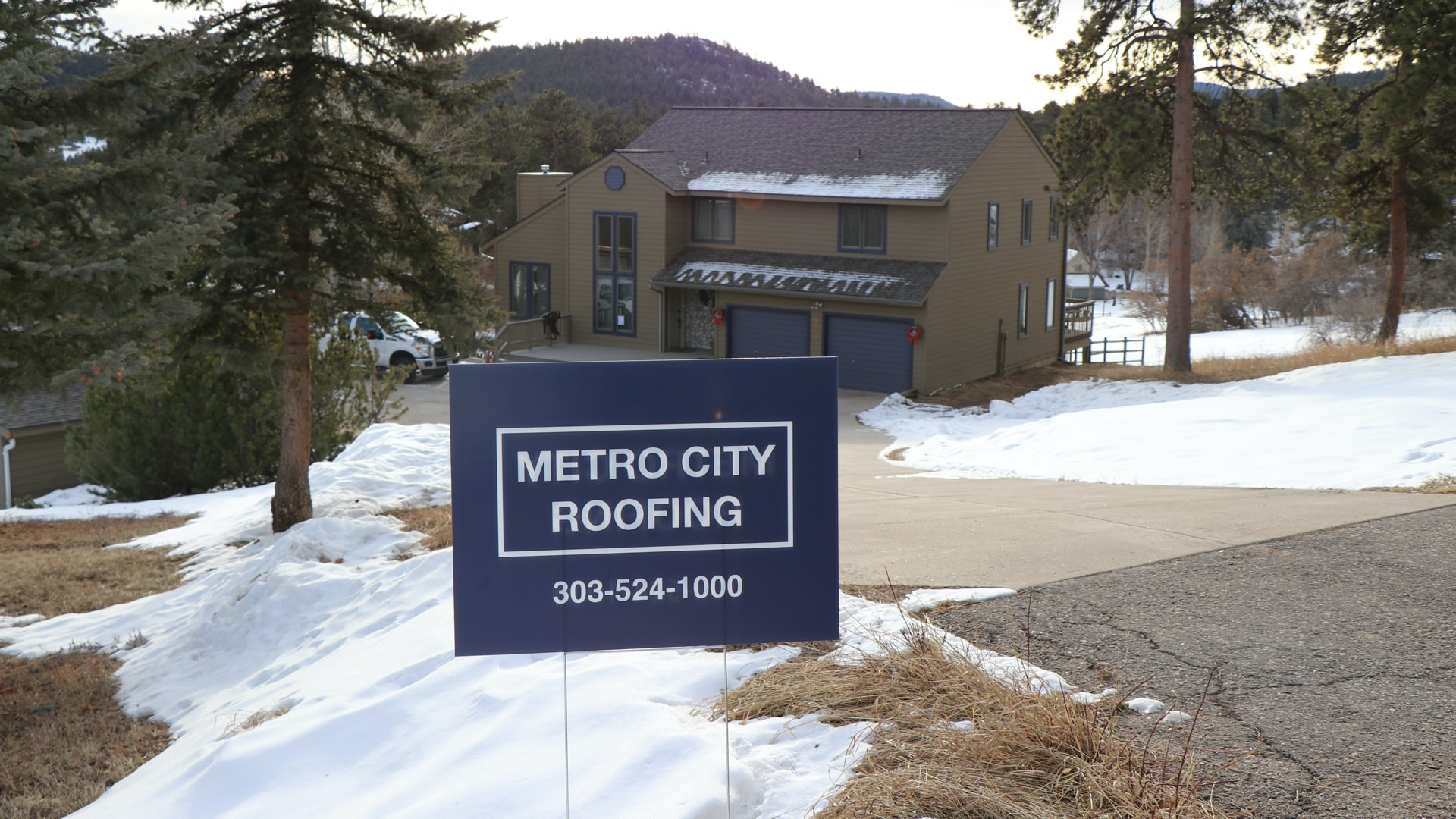 Brown, 2-story mountain home in Morrison, Colorado with long driveway and blue Metro City Roofing sign in the foreground