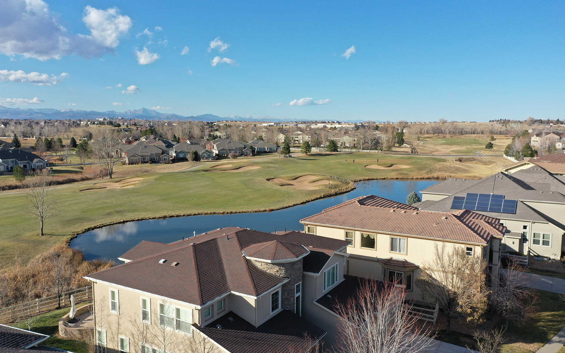 Aerial photo of a several large houses in the foreground with a golf course in the background in Broomfield, Colorado