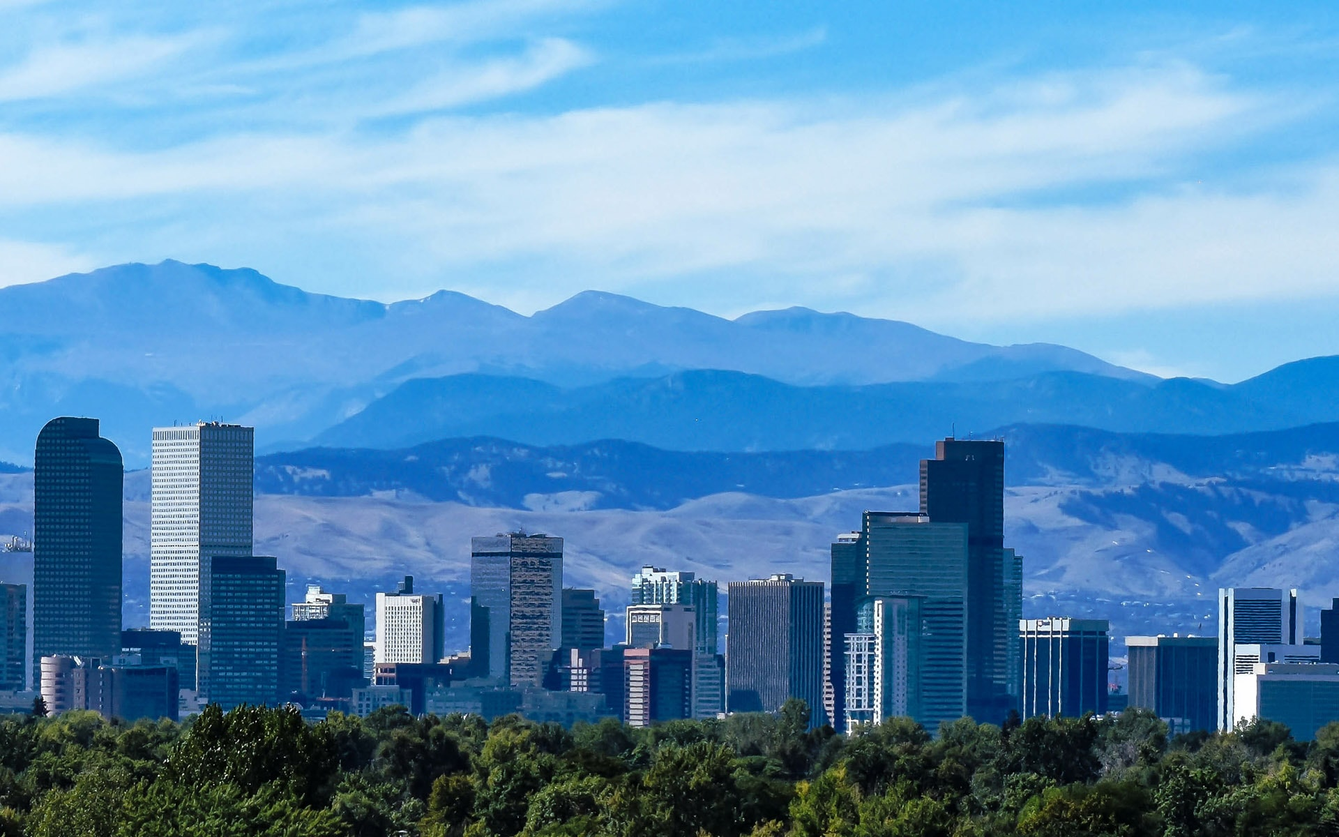 Aerial view of the Denver skyline with mountains and blue sky in the background