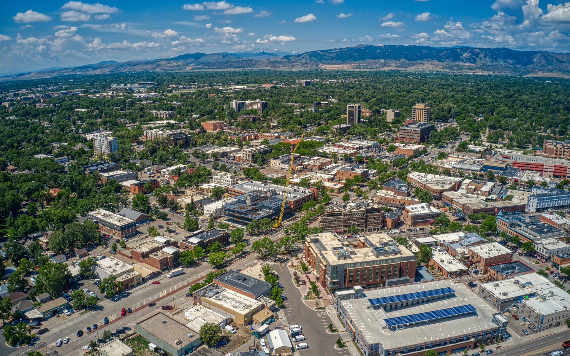 Aerial view of downtown Fort Collins, Colorado in the foreground with mountains and blue sky in the background