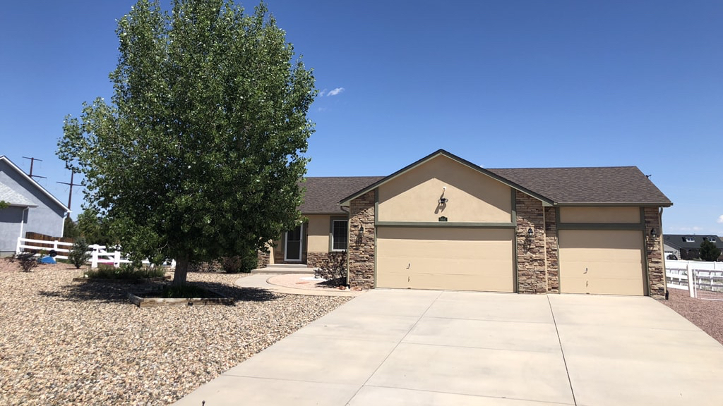 Tan paint and stone, ranch style home with dark brown roof in Peyton, Colorado with large driveway, gravel landscape, and one large green tree in the foreground and blue sky