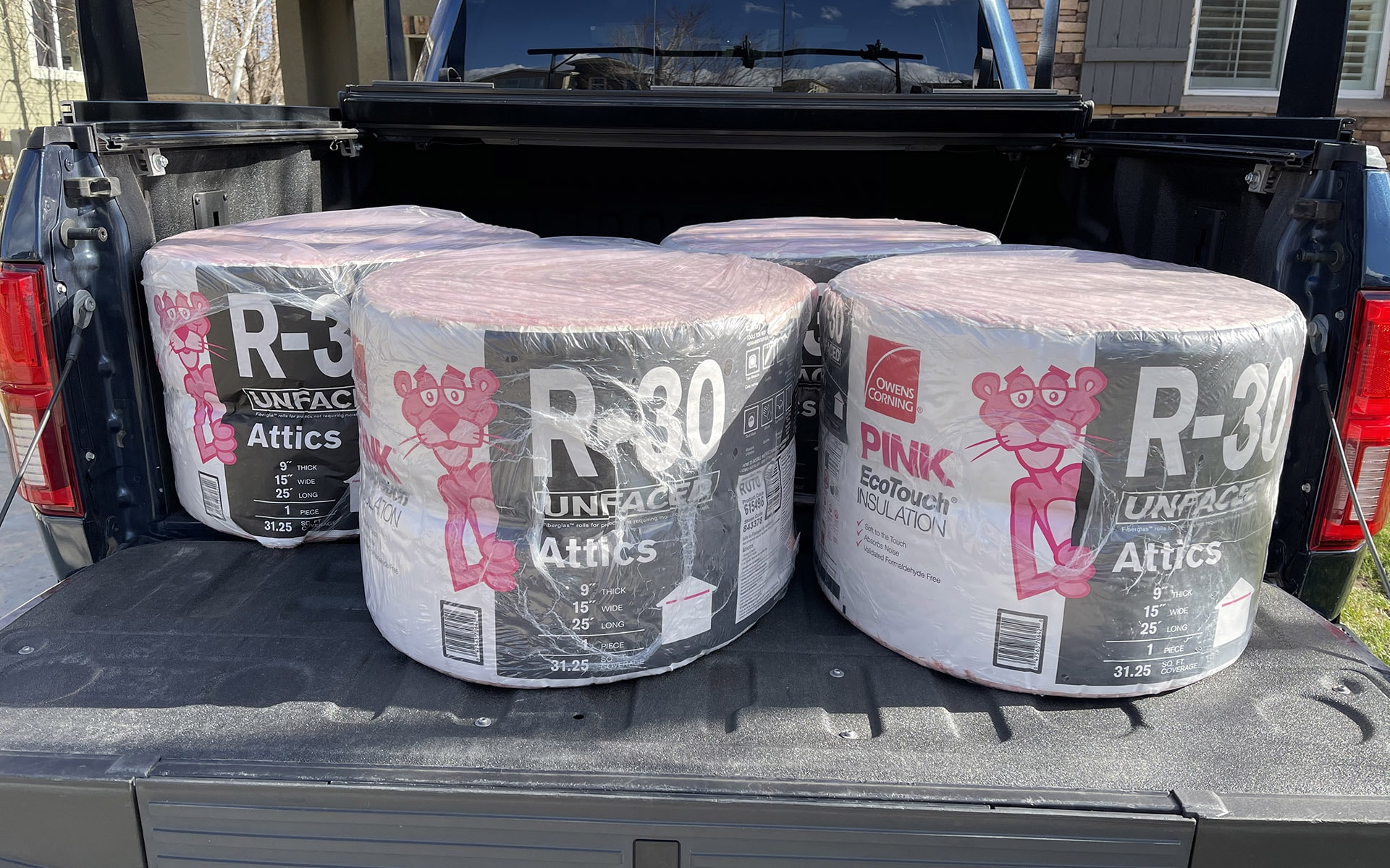 4 rolls of Owens Corning R-30 insulation in the back of a navy pickup truck in Broomfield, Colorado