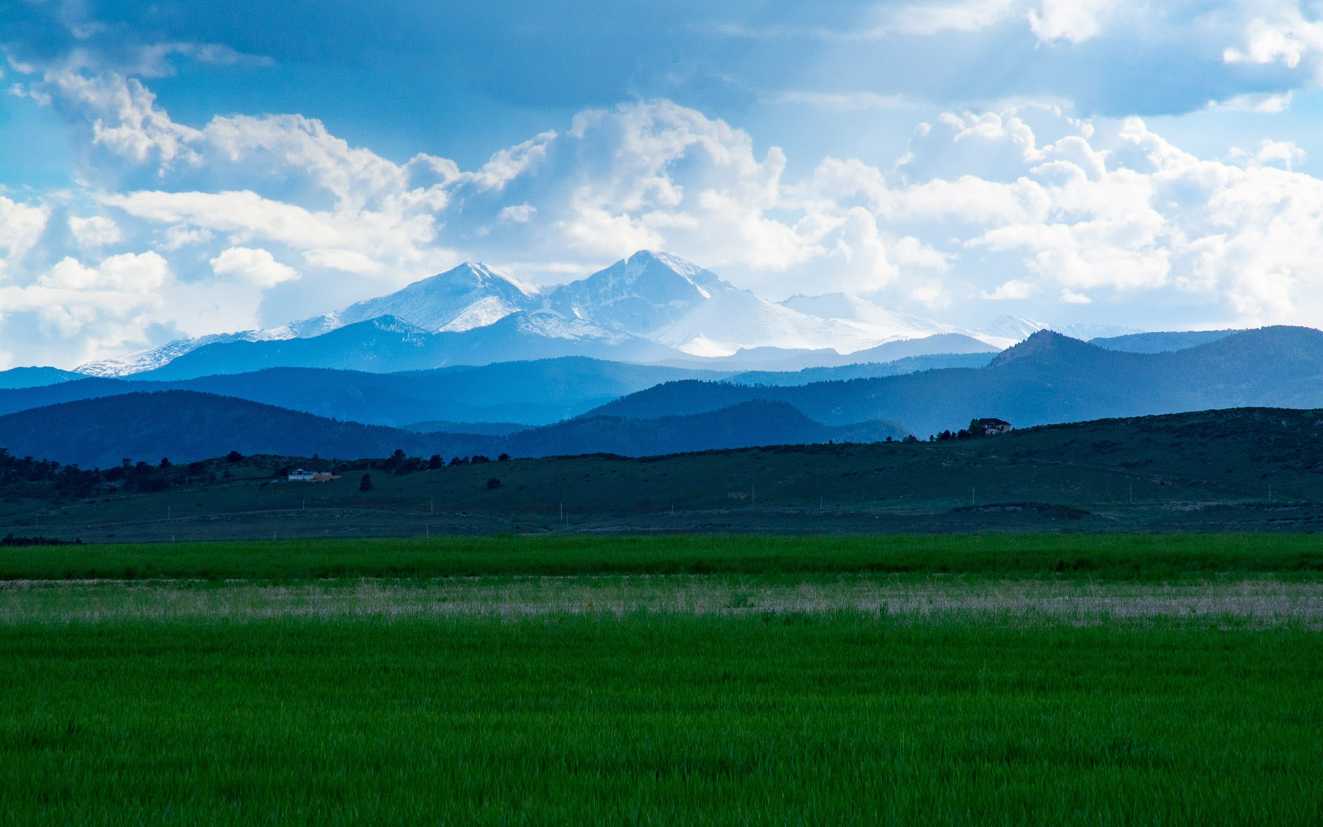 Rural green grass pasture in the foreground with mountains and blue sky and white clouds in the background