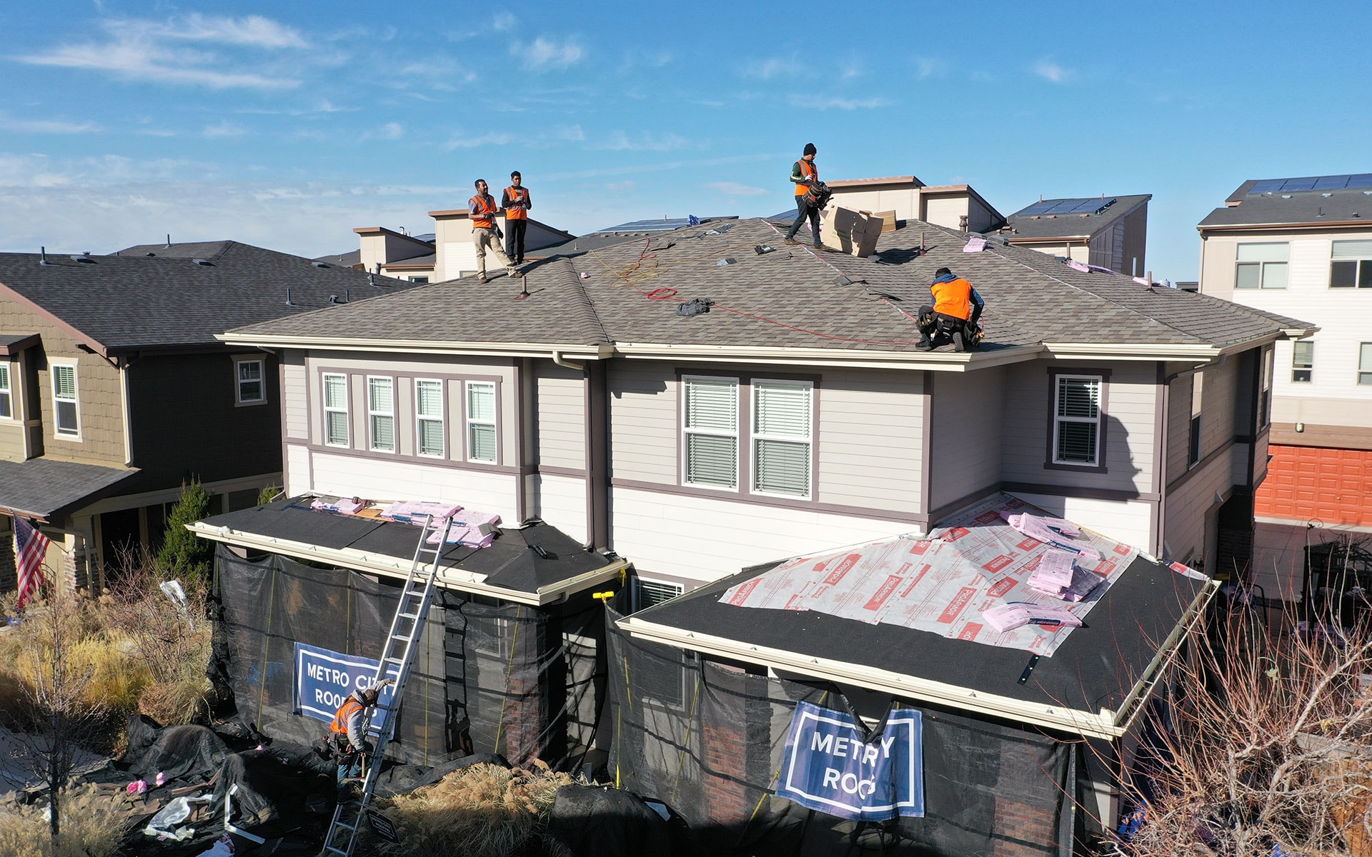 Metro City Roofing crew replacing the roof of a duplex in Denver, Colorado with five crew members working in orange vests with landscape protection kit in the front of the duplex