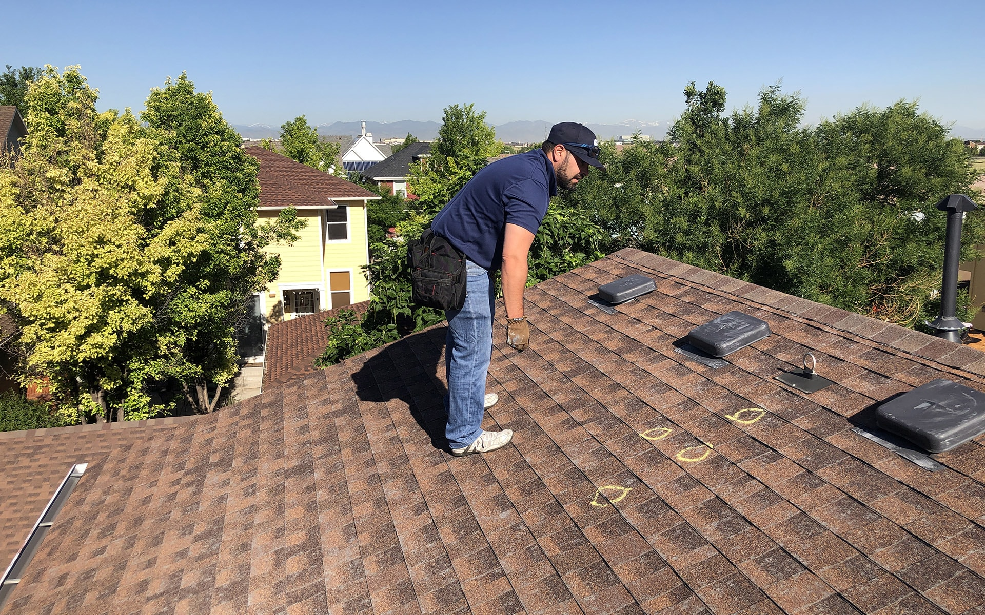 Metro City Roofing salesperson in a blue shirt and black hat inspecting a red shingle roof and marking hail impact marks in yellow chalk in Denver, Colorado with blue sky in the background