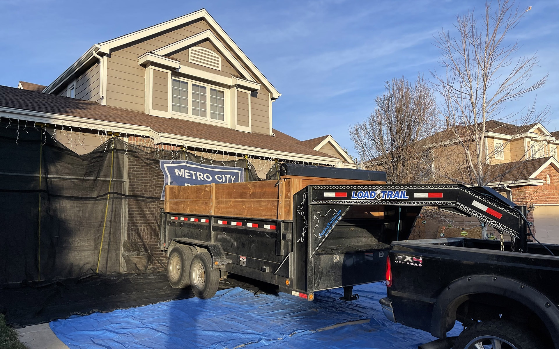 Metro City Roofing landscape protection kit with black roofing trailer backing up to house in the driveway in Littleton, Colorado